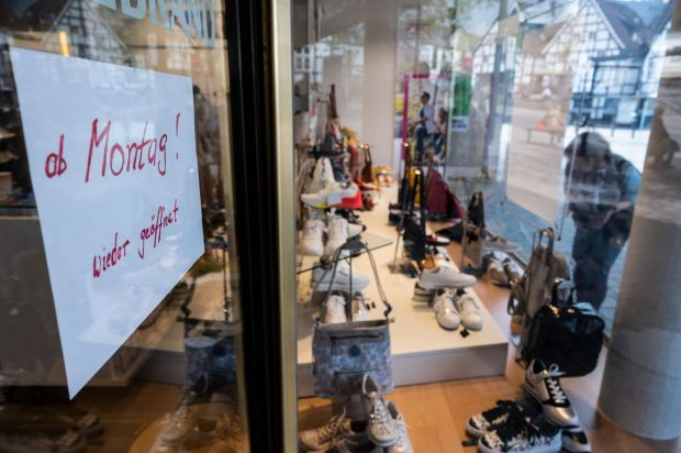 "Download von www.picturedesk.com am 28.04.2020 (14:26). 18 April 2020, North Rhine-Westphalia, Herdecke: ""Starting Monday! Open again"" is written on a slip of paper attached to the door of a shoe store. After the long break due to the coronavirus pandemic, many shops in NRW are being prepared for reopening. Photo: Bernd Thissen/dpa - 20200418_PD1610"